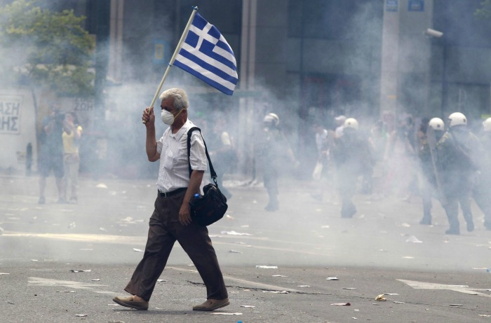 A protester holds a Greek as he walks in tear gas outside of the Greek Parliament in central Athens, during a rally against plans for new austerity measures, on Wednesday, June 15, 2011. A 24-hour strike by Greece's largest labor unions is set to cripple public services Wednesday, as the Socialist government begins a legislative battle to push through last-ditch cost cutting reforms that will exceed its own term in office.Demonstrators had camped outside parliament since May 25, 2011.  (AP Photo/Lefteris Pitarakis)